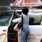 A passenger disembarks from a taxi that has Alibaba logos in Hong Kong
