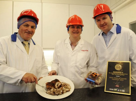 First Minister Arlene Foster, flanked by Dunbia's Jim Dobson and Michael Doran, samples some of the firm's award-winning pork