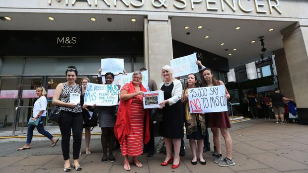 A group gathers outside Marks and Spencer's flagship store in Oxford Street, London, to hand in a petition calling on the high street giant to scrap proposed pay cuts to offset the cost of the National Living Wage