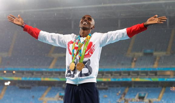 Great Britain's Mo Farah celebrates with his gold medals after winning the Men's 5000m and 10,000m at the Olympic Stadium on the fifteenth day of the Rio Olympic Games, Brazil