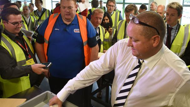 Sports Direct founder Mike Ashley empties his pockets of bank notes during a mock search at the Sports Direct headquarters in Shirebrook, Derbyshire.