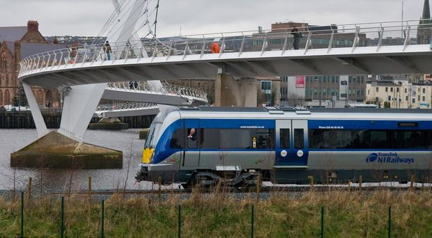 A train passes under the Peace Bridge in Derry. An integrated hub is planned for the old Waterside station