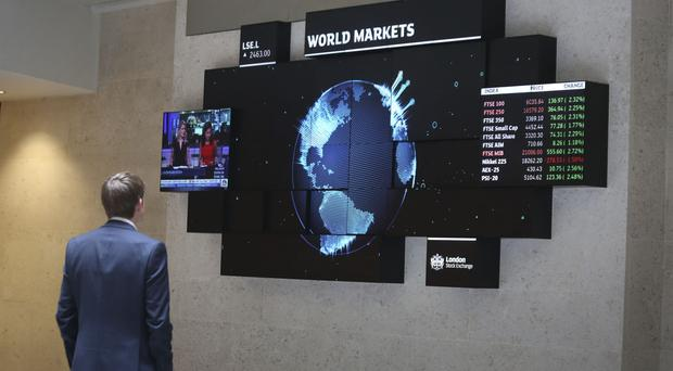 A city worker looking at a stock ticker screen at the London Stock Exchange