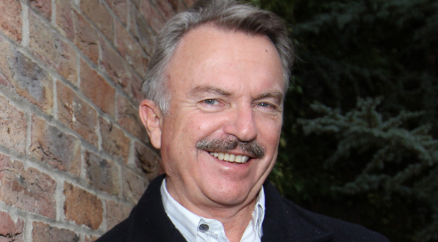 Actor Sam Neill with a bottle of his Two Paddocks Pinot Noir during a visit to Northern Ireland