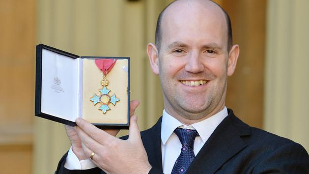 Dr Eben Upton holds his CBE