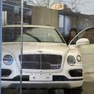 A woman looks at a luxury car displayed at Bentley Motors showroom in Beijing (AP)