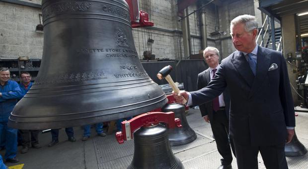 The Prince of Wales strikes the Charles bell during his visit to the Whitechapel Bell Foundry