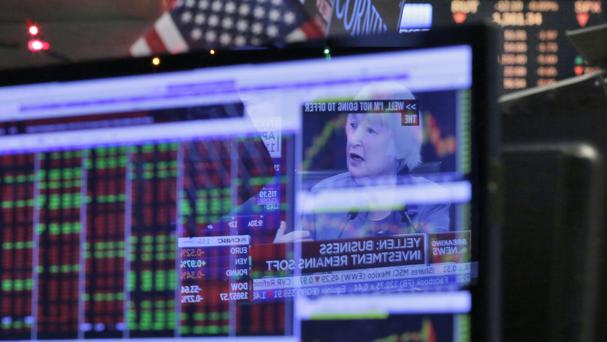 Federal Reserve Chair Janet Yellen's news conference in Washington is reflected on a specialist's screen on the floor of the New York Stock Exchange (AP)