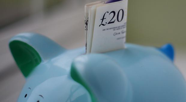 Money in a piggy bank at a home in Ashford, Kent.