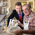 Belleek managing director John Maguire looks on as master craftsman Brendan McCauley works on a figurine