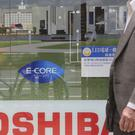 A man walks past a display of Toshiba products as the company said chairman Shigenori Shiga will step down from the board but will remain as an executive (AP Photo/Koji Sasahara)