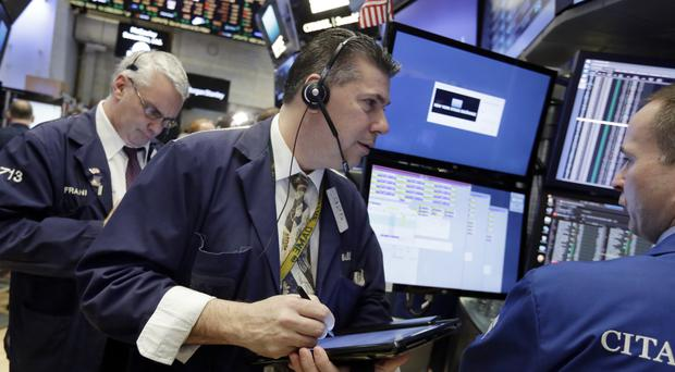 Trader William McInerney works on the floor of the New York Stock Exchange (Richard Drew/AP)