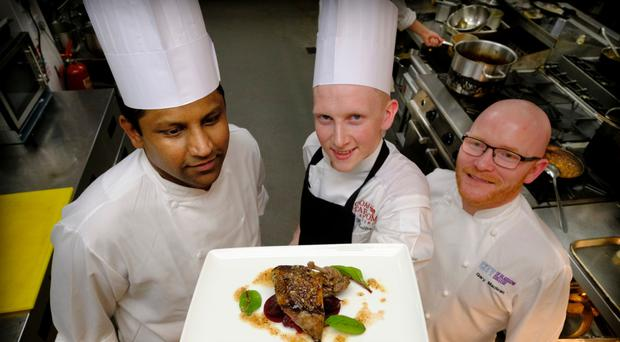 Max Buller (centre) shows off his new skills, with chefs Barath Kumar (left) and Gary Maclean