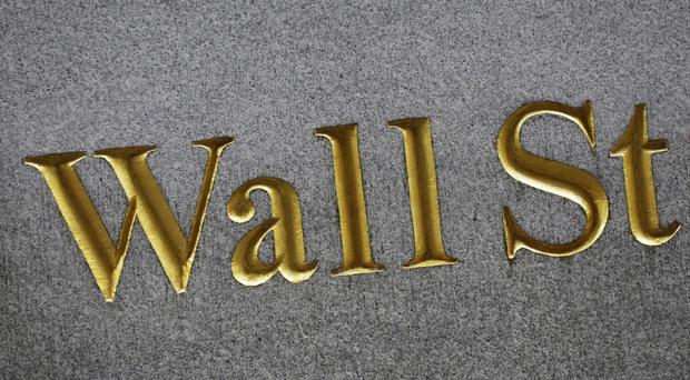 A sign for Wall Street carved into the side of a building in New York (AP Photo/Mark Lennihan, File)