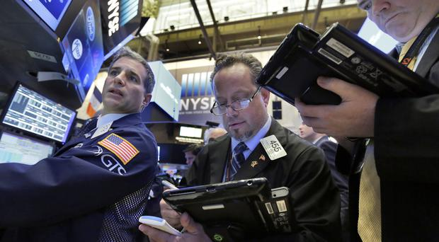 Specialist Anthony Rinaldi, left, works with traders Robert Arciero, centre, and James Conti at his post on the floor of the New York Stock Exchange (AP)