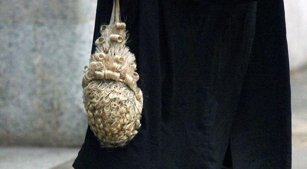 A lawyer holding his wig outside the Old Bailey