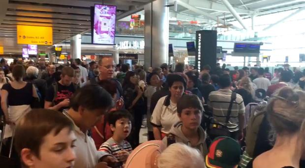 Passengers queue at Heathrow airport's terminal 5 after British Airways cancelled flights because of IT problems