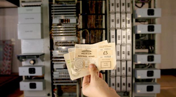 Premium bonds from the 1960s and 1970s are held up in front of Ernie 1, the Premium Bond number generator