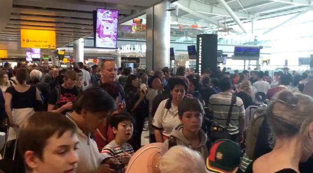 Passengers queuing at Heathrow airport Terminal Five.