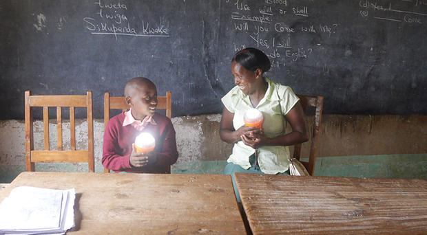 Faith Mutiti and her son Dennis, who are beneficiaries of a scheme to bring solar lights to remote communities in East Africa (FTI Consulting/PA)