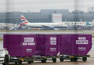 A British Airways plane on the runway behind cargo containers adorned with 'Britain's New Runway', at Heathrow Airport as a third runway at the airport has been given the go-ahead by the government