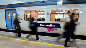 Commuters make their way past a Thameslink train on the platform at Blackfriars Station, London, in the morning rush hour.