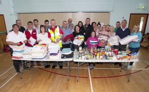 Eglinton Community Centre manager Debbie Caulfield (front centre) with local volunteers, council officials, church representatives, Red Cross volunteers and Salvation Army representatives with some of the donated clothes and food supplies