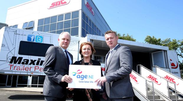 Chris McCauley (left) and Enda Cushnahan of SDC Trailers congratulate Siobhan Casey of Age NI after it became the firm's nominated charity in 2017