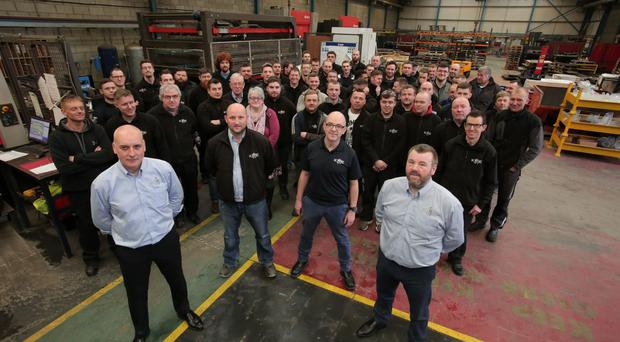 KME Steelworks directors Seamus Murchan (front left) and Jason Quinn (right) mark the end of a high growth year with staff at the Lisburn plant