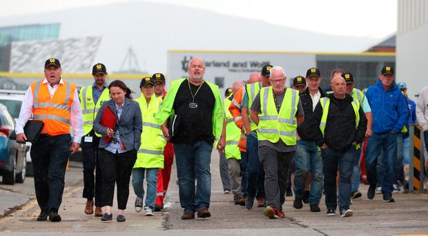 Harland & Wolff workers emerge from a meeting yesterday chanting 'save our shipyard'
