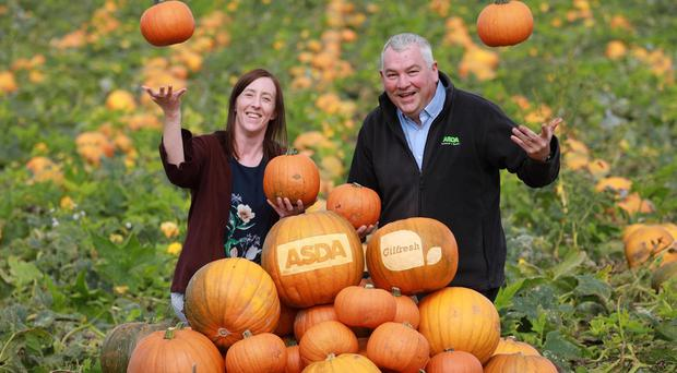Danielle Mitchell of Gilfresh and Billy Clelland from Asda celebrate the first pumpkin harvest in Loughgall, Co Armagh