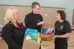 Debbie Caulfield (right), of Eglinton Community Centre, receives food donated by staff at Longs Supermarket from Elaine Lynch and James Martin
