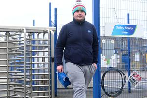A worker walks out at Moy Park in Portadown yesterday. Around 100 of the firm's 1,000 workforce left