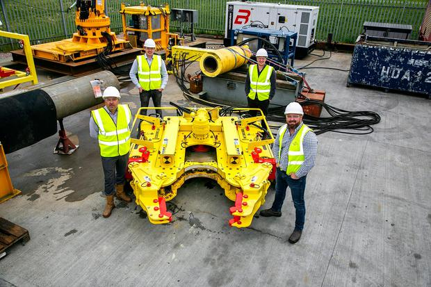 """Cutting edge: From left, Decom Engineering's new 24"""" chopsaw and (l to r) business development managers Scott Eke and Matthew Drumm, commercial director Nicholas McNally and chief executive Sean Conway. Credit: Rory Raitt"""