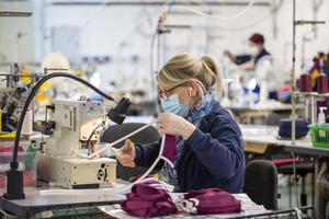 Member of staff at O'Neills in Strabane works on scrubs after the business has diversified from GAA jerseys