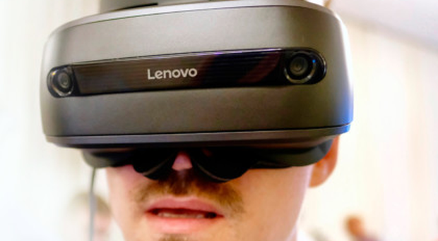 A visitor tries out the Lenovo Explorer mixed reality' headset at the IFA consumer electronics show in Berlin