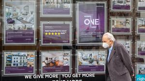 A man wearing a protective face mask passes an estate agents window in Knightsbridge, London (Dominic Lipinski/PA)