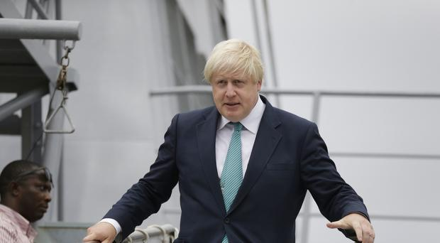 British Foreign Secretary Boris Johnson walks down from a Nigeria Naval warship after a visit to the Nigeria Navy at the Naval dockyard in Lagos, Nigeria.