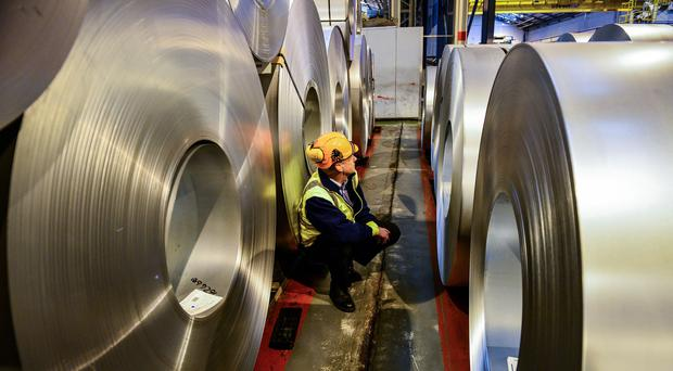 A worker inspecting rolls of steel (PA)