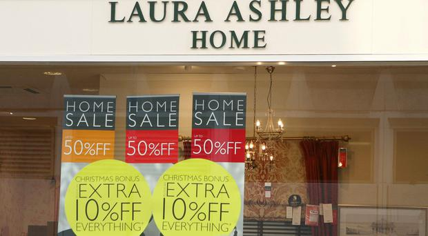 Laura Ashley has warned over full-year profits after half-year earnings slumped due to falling sales and the weak pound.