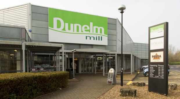 Dunelm Mill has seen shares hit after half-year profits were held back by hefty discounting and its recent Worldstores acquisition.