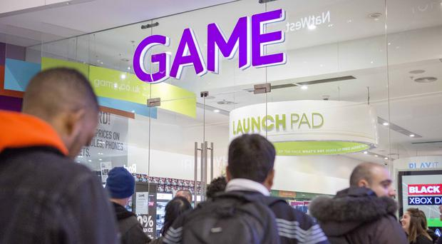 Shoppers wait outside the entrance to leading games retailer GAME in Westfield shopping centre in Stratford (PA)