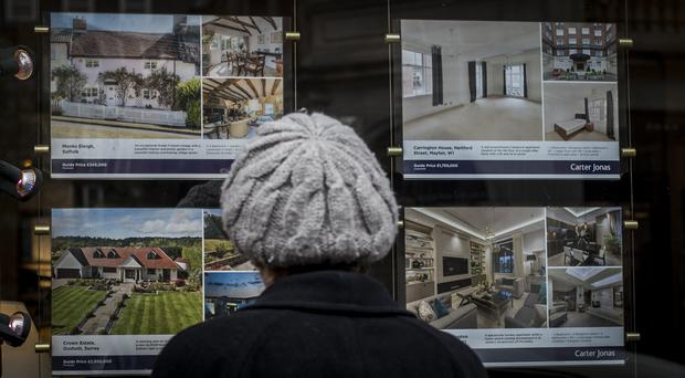 A woman looks at houses for sale in the window of an estate agents in Mayfair, London (Lauren Hurley/PA)