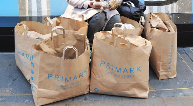 A woman, surrounded by Primark bags, sits on the window ledge of Primark at Marble Arch, in Oxford Street, central London.