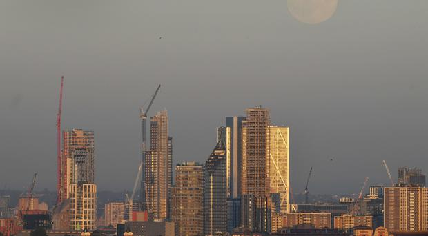 The view from Parliament Hill in Hampstead, London of the moon rising over the City of London, ahead of the Full Moon in the early hours of Thursday morning, which is known as a Strawberry Moon.