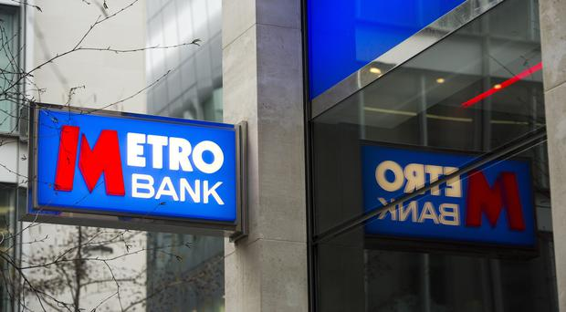 A Metro Bank sign hangs above a branch window, London.