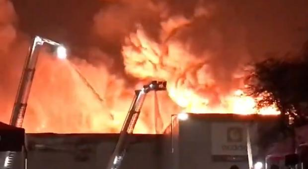Undated handout photo taken with permission from the Twitter feed of @lottielouises of firefighters tackling a huge fire that swept through an Ocado robotic warehouse in Andover, Hampshire, as it has been brought under control more than a day after it first broke out.
