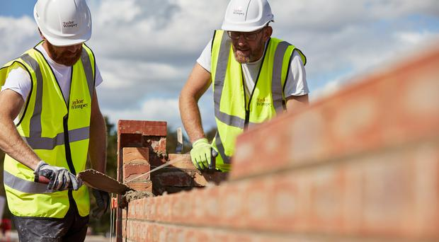 Undated Taylor Wimpey handout photo of workers laying bricks at a Taylor Wimpey construction site.