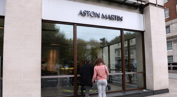 Passers-by look in the window of Stratstone's Aston Martin Mayfair dealership on Park Lane, London, whose parent company, Pendragon, has seen boss Mark Herbert quit after just three months (PA)
