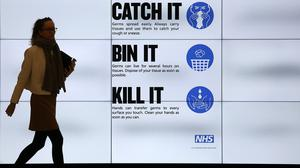 An NHS catch it, bin it, kill it sign on TV screens in the entrance to the QEII Centre in London (Philip Toscano/PA)